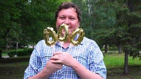 Hombre grande que sostiene los globos de oro que hacen el número 000 al aire libre 000o partido de la celebración del aniversario almacen de video