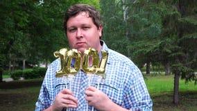 Hombre grande que sostiene los globos de oro que hacen el número 1001 al aire libre 1001o partido de la celebración del aniversar almacen de video