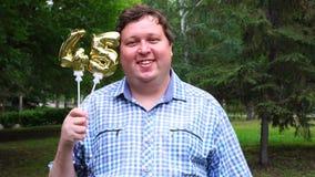 Hombre grande que sostiene los globos de oro que hacen el número 45 al aire libre 45.o partido de la celebración del aniversario almacen de video
