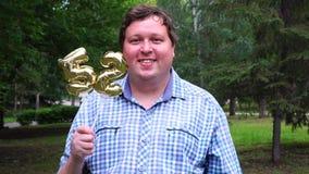 Hombre grande que sostiene los globos de oro que hacen el número 52 al aire libre 52o partido de la celebración del aniversario almacen de metraje de vídeo
