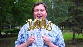 Hombre grande que sostiene los globos de oro que hacen el número 1000 al aire libre 0o partido de la celebración del aniversario metrajes