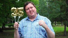Hombre grande que sostiene los globos de oro que hacen el número 35 al aire libre 35to partido de la celebración del aniversario almacen de video