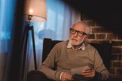 hombre gris hermoso del pelo que se sienta en la butaca, sosteniendo las fotos viejas Foto de archivo libre de regalías