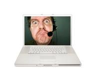 Hombre gruñón del servicio de atención al cliente en la pantalla de la computadora portátil Foto de archivo