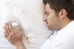 Hombre gruñón en la cama que apaga el despertador imágenes de archivo libres de regalías
