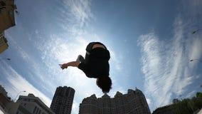 Hombre hacer salto mortal hacia atr?s acrob?tico sobre el fondo del cielo azul, c?mara lenta estupenda metrajes