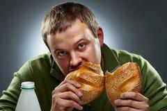 Hombre hambriento con la boca llena de pan Foto de archivo libre de regalías