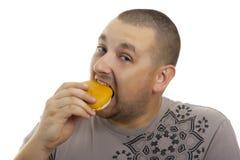 Hombre hambriento con la hamburguesa. foto de archivo