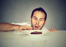 Hombre hambriento que anhela la comida dulce foto de archivo