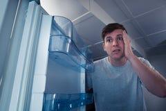 Hombre hambriento que mira en refrigerador Imágenes de archivo libres de regalías