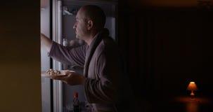 Hombre hambriento que mira en un refrigerador que toma la placa con la comida el tiro de comportamiento divertido de la noche en  metrajes