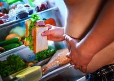 Hombre hambriento que sostiene un bocadillo en sus manos y situación al lado de foto de archivo libre de regalías