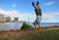 Hombre Handstanding a lo largo de la orilla de la isla mágica Imagenes de archivo