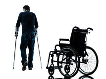 Hombre herido con las muletas que se niega a afrontar silhou de la silla de ruedas Foto de archivo