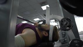 Hombre herido en el gimnasio que siente dolor agudo en el brazo, barbell de elevación en la prensa de banco metrajes
