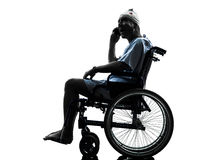 Hombre herido en el teléfono sorprendido en silueta de la silla de ruedas Fotos de archivo libres de regalías