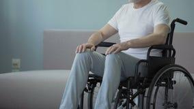 Hombre herido en silla de ruedas en el centro de rehabilitación de la salud, esperanzas de caminar otra vez almacen de metraje de vídeo
