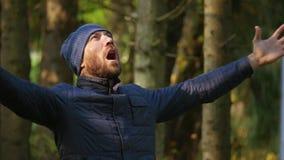 Hombre hermoso acertado al aire libre que aumenta sus manos que gritan en alta voz puesta del sol de oro hermosa almacen de metraje de vídeo