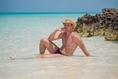 Hombre hermoso acertado feliz con el cigarro en la playa, Océano Atlántico, Cuba, Playa Pilar, Cayo Guillermo Imagenes de archivo