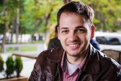 Hombre hermoso adulto joven que se sienta en el café o restaurante y sonrisa de la calle Imagen de archivo libre de regalías
