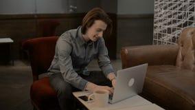 Hombre hermoso afortunado que trabaja en un ordenador portátil, hombre que mecanografía en un ordenador portátil metrajes
