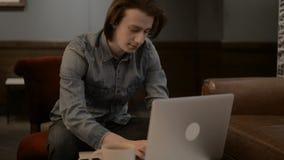 Hombre hermoso afortunado que trabaja en un ordenador portátil, hombre que mecanografía en un ordenador portátil almacen de video
