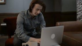 Hombre hermoso afortunado que trabaja en un ordenador portátil, hombre que mecanografía en un ordenador portátil almacen de metraje de vídeo