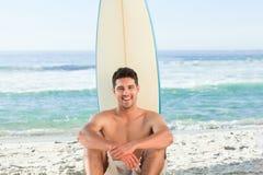 Hombre hermoso al lado del mar con su tabla hawaiana Imágenes de archivo libres de regalías