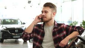 Hombre hermoso alegre que habla en el teléfono en la concesión de coche almacen de video