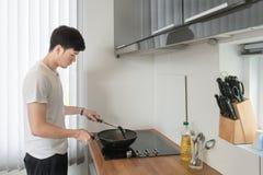 Hombre hermoso asiático que cocina en la cocina en casa Imagen de archivo