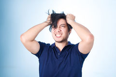 Hombre hermoso asiático que lleva a cabo a su cabeza que frunce el ceño con la preocupación pulling fotos de archivo libres de regalías