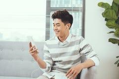 Hombre hermoso asiático sonriente que se sienta en el sofá acogedor que escucha el mus Foto de archivo