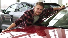 Hombre hermoso barbudo alegre que abraza su nuevo auto en el salón de la representación almacen de metraje de vídeo