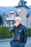 Hombre hermoso barbudo joven con besos jacketsending del sombrero y del cuero en fondo de la casa rosada vieja hermosa en la mont Imagenes de archivo
