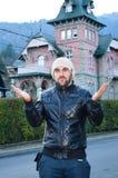 Hombre hermoso barbudo joven que envía besos en fondo de la casa rosada vieja hermosa en la montaña Foto de archivo