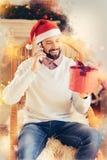 Hombre hermoso barbudo que llama a su novia que le invita para la cena de la Navidad foto de archivo