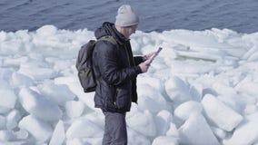 Hombre hermoso barbudo rubio joven en la situación caliente de la chaqueta y del sombrero en el glaciar que comprueba con el mapa metrajes