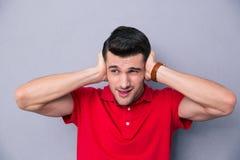 Hombre hermoso casual que cubre sus oídos Imagen de archivo