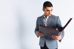 Hombre hermoso con el hombre de la carpeta que lee un menú, individuo elegante del negocio en traje en estudio en el fondo blanco fotografía de archivo libre de regalías