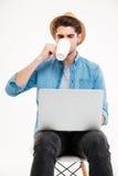 Hombre hermoso con el ordenador portátil que se sienta en silla y el café de consumición Fotos de archivo libres de regalías