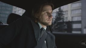Hombre hermoso con el pelo marrón en camisa del pistacho y el montar a caballo gris del traje en cinturón del coche y de segurida metrajes