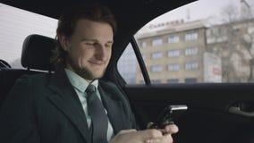 Hombre hermoso con el pelo marrón en camisa del pistacho y el montar a caballo gris del traje en coche y mensaje que mecanografía metrajes