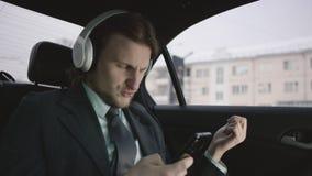 Hombre hermoso con el pelo marrón en camisa del pistacho y el montar a caballo gris del traje en coche y mensaje que mecanografía almacen de video