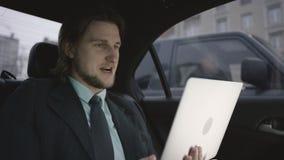Hombre hermoso con el pelo marrón en camisa del pistacho y el montar a caballo gris del traje en coche y trabajo sobre su cuadern almacen de metraje de vídeo