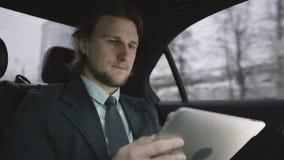 Hombre hermoso con el pelo marrón en camisa del pistacho y el montar a caballo gris del traje en coche y el trabajo con su tablet metrajes