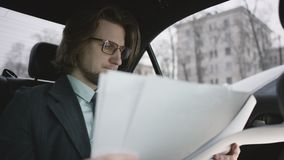Hombre hermoso con el pelo marrón en la camisa del pistacho y traje gris y vidrios que montan en coche y que leen documentos almacen de video