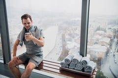 Hombre hermoso con el teléfono móvil y la toalla que tienen una rotura después de entrenamiento en gimnasio Fotografía de archivo