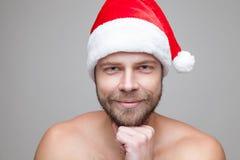 Hombre hermoso con la barba que lleva un sombrero de la Navidad Imagenes de archivo