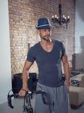 Hombre hermoso con la bicicleta en el hogar de moda Imagenes de archivo