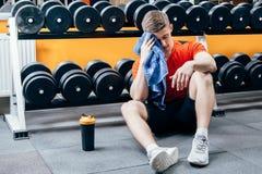 Hombre hermoso con la botella de agua y de toalla que tienen una rotura después de entrenamiento en gimnasio Imagen de archivo libre de regalías
